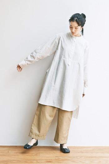 ベージュのワイドパンツに、白のシャツチュニックをレイヤードしたコーディネートです。ひざの少し上ぐらいまですっぽりと隠してくれるので、体型カバーにもぴったりなスタイリングです。足元は黒のフラットシューズで、ナチュラルコーデに引き締めポイントをプラス。