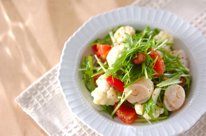 ホタテとグレープフルーツ、カリフラワーとトマトを水菜で和えたサラダです。フレッシュなジューシーさがたまらない、お酒のつまみとしても美味しくいただけるひと品です。  白の割合が多くなりすぎるとぼんやりとした印象になってしまいがち。トマトはホタテとカリフラワーよりも気持ち小さめにカットして、アクセントとして使うと見た目が締まり、完成度がアップしますよ。
