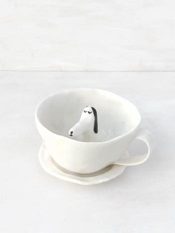 カップからひょこっり顔を出しているのは、うたたねしている犬! イラストレーターで陶芸家のエレオノール・ボストロムのシンプル可愛いティーカップ&ソーサーです。 作家自身の手で形成されていて、手作りの風合いも素敵です。