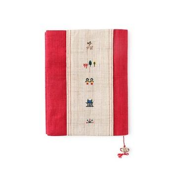 奈良絵とは、元々はお釈迦様の生涯を絵物語で表したものですが、現代では奈良の風景や鹿、昔の物語などといった、色々な紋様が組み入れられています。その奈良絵を刺繍であしらったブックカバー。中川政七商店の鹿のタグとも好相性です。ブックマークのコロンとした陶玉が愛らしいですね。