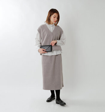 ニットスカートでは珍しいラップデザインのニットスカート。ミモレ丈なので足さばきも良く、歩く度にふわりとした動きも楽しめそう。同系色のベストから、さりげないフリルが素敵なシャツをのぞかせてアクセントに。