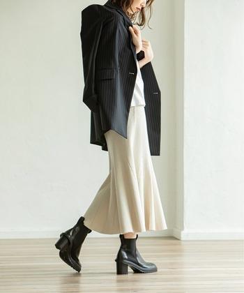 ウエストラインはほっそりタイトで、裾がふんわりと広がったマーメードラインのニットスカート。メンズライクなテーラードジャケットを羽織れば、引き締まったスタイリングに。
