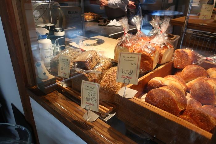 """小さな店舗に気持ち良く並ぶのは、自家製発酵種を用いて水を多く加えた生地で焼き上げる""""サワードゥ・ブレッド""""。 サワードゥのパンは、一般的に硬く、酸味があるというのが定説になっていますが、当店のパンは""""高加水""""で、国産小麦を使用するため、皮が薄く、大小様々の気泡が綺麗に入り、モチモチして柔らかいのが特徴です。"""