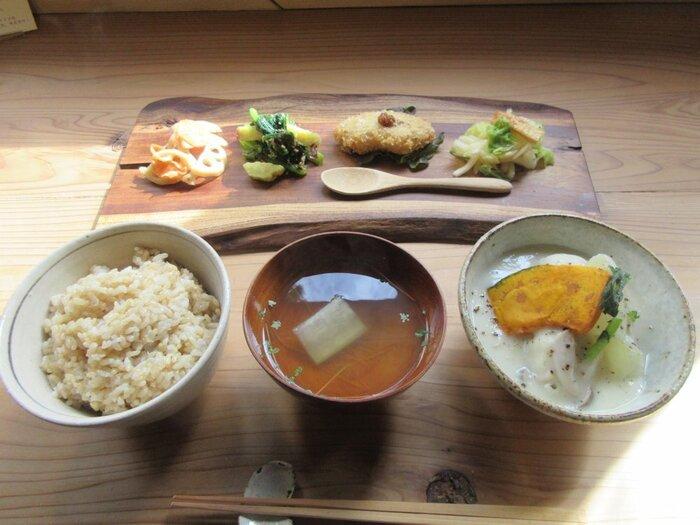 """「日日食堂」は、空間も、調度品も、器も、時間も、全てひっくるめた食空間。広い店内では、日本人が培ってきた感性や知恵を取り入れた手作り料理がゆったりと味わえます。  食堂で提供されるのは、出汁・玄米・土鍋ごはん・オーガニックの家庭料理がメイン。節気で変わる『二十四節気ごはん』や、地元で揚がる新鮮な魚を用いた、フライや竜田揚げの定食など。  【旬の食材を用いた惣菜とご飯と汁物の和食膳『二十四節気のごはん』。画像は、秋の""""霜降(そうこう)""""時のもので、カリフラワーのすり流しシチュー風、白菜とお揚げの柚子マリネの他、きんぴらや車麩のフライ、胡麻和え等などが盛り付けられている。】"""
