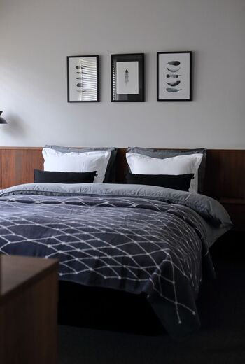 クッションを並べて、ベッド周りをホテルライクな空間に。素敵なアートを飾れば、眠っている時以外にも眺めるだけで癒やされる場所になりますね。