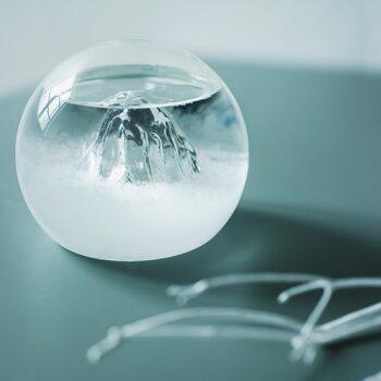 ふわふわの結晶が雲海のように見える、ユニークなデザインのストームグラス。見る角度によって変わる山の姿が味わい深く、自然を感じるアートオブジェのようです。