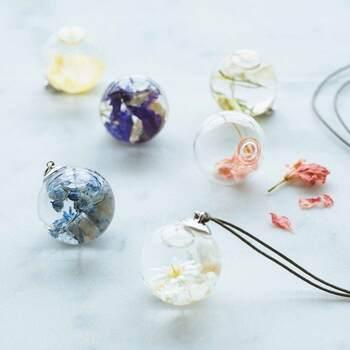 スノードームのように球体の中でお花が揺らめく、小さめサイズのハーバリウムチャーム。レンズ効果で花が拡大されるます。付属のコードで窓辺に吊るしたり、ガーランドのアクセントにしたりとさまざまな飾り方を楽しんでみましょう。
