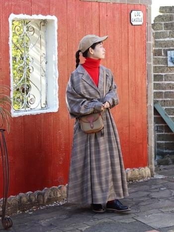 まるでワンピースのようなシルエットのコートは、レトロな雰囲気を感じさせます。コーデにポイントとして赤いハイネックのニットを合わせましょう。寒い冬も明るい気持ちになれそうですね。