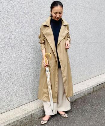 ロングトレンチレインコートを使ったきれいめ通勤コーデ。天候にかかわらず毎日のワードローブに取り入れたくなる長め丈のコートとアンクル丈のワイドパンツを合わせて、足元の汚れも防ぐコーデに仕上げています。