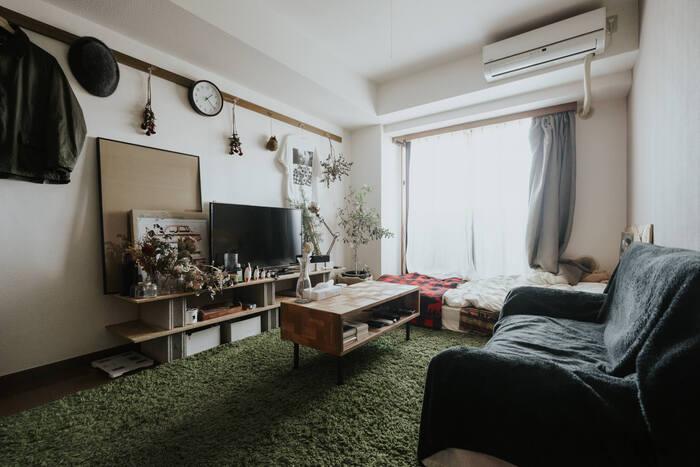 暗色ソファは存在感が出てお部屋を窮屈にしがちですが、ラグのトーンをシックにすることで重心が床面になり、広さを感じるコーディネートとなっています。壁の白さがさりげなく生かされた色使いです。