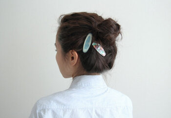 1つにまとめたお団子ヘアにヘアクリップを付けたアレンジです。後れ毛をまとめたり、ほつれるのを防いだりしてくれながら、華やかさを添えています。