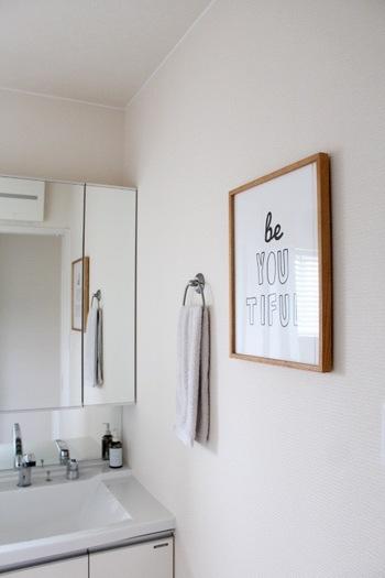 洗面所の白壁が少し寂しく感じたら、フレームアートをプラスしてみてはいかがでしょう。写真のように、シンプルなロゴのみのアートなら、空間に溶け込みながらスタイリッシュな雰囲気を演出します。