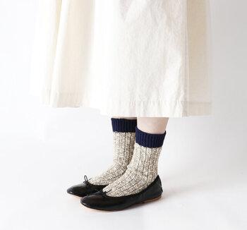 色の太さがランダムで味のあるスラブ糸を使って織られた靴下です。厚手の綿素材なので、寒くなるこれからの季節にもぴったり。履き口のネイビーの配色切り替えが、ほどよいワンポイントになっています。