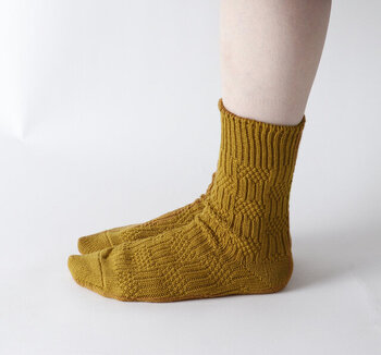 凸凹感のある立体的な編み柄が、ちょっぴり個性的なマスタードカラーの靴下です。柔らかいコットン糸を使用し、伸縮性に優れているのがポイント。差し色としても活躍してくれます。
