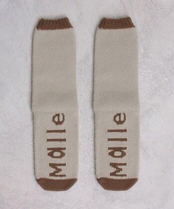 ウール混のあったか素材で作られた、ロゴ入りのベージュ靴下です。履き口とつま先にトーン違いのベージュを配色して、シンプルになりすぎないデザインに仕上げています。