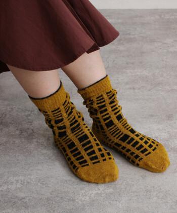 キャメルカラーに、格子柄のデザインを組み合わせた靴下。モール糸を素材に採用しているため、毛足が長く厚みとボリューム感のある仕上がりです。履くだけで暖かさを感じられるので、これからの季節にワンポイントとして活用したいアイテムですね。