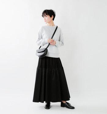 シンプルなグレーのスウェットに、黒のフレアスカートを合わせたコーディネート。カジュアルなスウェットコーデを、ローファーシューズで大人スタイルに格上げ♪
