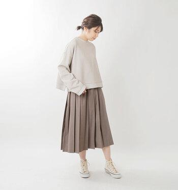 ベージュのスウェットトップスに、ブラウン系のプリーツスカートを合わせたコーディネートです。ミディ丈のスカートにスニーカーを合わせて、程よく素肌見せをしているのがポイント。寒い日には、タイツなどを合わせても◎