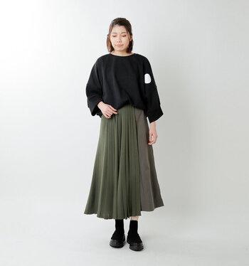 黒のスウェットトップスを、カーキカラーのスカートにタックインしたコーディネートです。ゆったりシルエットとのトップスは、ボトムスにタックインすることで上半身をすっきり見せられます。足元は黒のシューズで、統一感のあるスタイリングに。