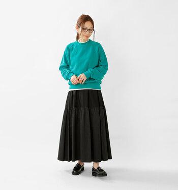 キレイめグリーンのスウェットに、黒のプリーツスカートを合わせた着こなし。スウェットの下からさりげなく白インナーをチラ見せして、今っぽさをプラスしています。