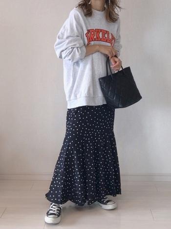 ネイビーのドット柄スカートに、グレーのロゴ入りスウェットを合わせたコーディネート。足元はスニーカーで、柄スカートをとことんカジュアルなスタイリングに仕上げています。手に持った黒のハンドバッグで、大人っぽさをさりげなくプラス。