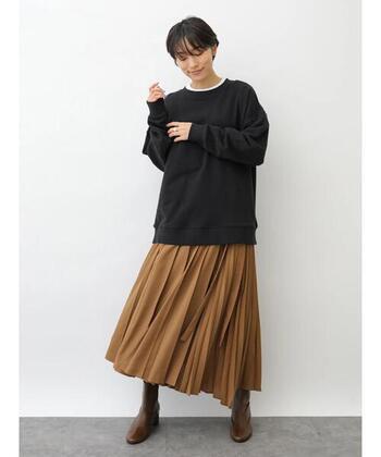 黒のスウェットトップスに、ブラウンのスカートを合わせたコーデ。足元は同じくブラウンのブーツで色を合わせて、脚を長く見せる効果も期待できます。襟からさりげなく覗かせた白インナーで、トレンドを感じさせるエッセンスをプラス。