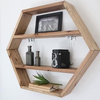 こちらの大きめの棚も壁に取り付けています。釘などで取り付けるのではなく、穴が目立ちにくいように専用の金具とホッチキスで留めると、賃貸でも気軽に取り付けられますよ。六角形のフォルムのヘキサゴンラックに、カメラや雑貨を置いてディスプレイコーナーに。