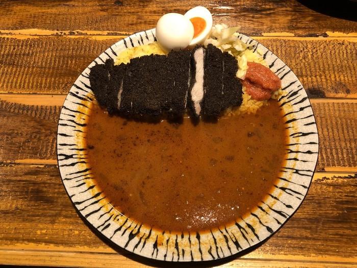 黒いカツがインパクト大の「マハーカツカレー」。イカ墨の入った衣をつけて揚げられたロースカツはサクサク香ばしく、カレーとの相性も抜群です。上に乗った卵はゆで卵ではなく、甘酸っぱい卵のピクルス。ルーはスープカレーのようにさらさらとしていてコクがあり、カツやご飯によく馴染みます。