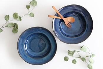 一枚で料理が完結するお皿なら、他のお皿との組み合わせを考える必要がなく、好きなものを好きなように取り入れることができます。こちらのお皿は 岐阜県の東濃地方で作られる美濃焼によるもので、海鼠釉を使用し、深い海のようなインディゴブルーを出しているのが魅力。一皿一皿手作りだからこそ異なる輪郭も、使えば使うほどいとおしく感じられます。