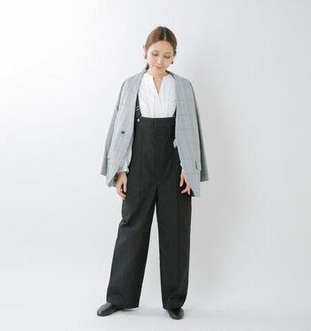 黒のワイドシルエットサロペットに、白ブラウスとジャケットを合わせたコーディネート。メンズライクな印象を与えるシックなカラーリングで、サロペットをクールに着こなしています。