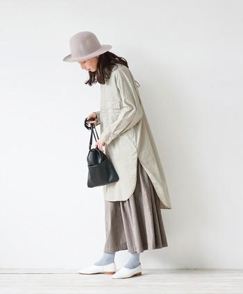 薄いグレーのワンピースに、トーン違いのグレースカートを重ねたスタイリングです。ハットや靴下もグレー系で色味を合わせて、全体的に統一感のある着こなしに。黒のバッグと白のシューズが、程よいアクセントカラーになっています。