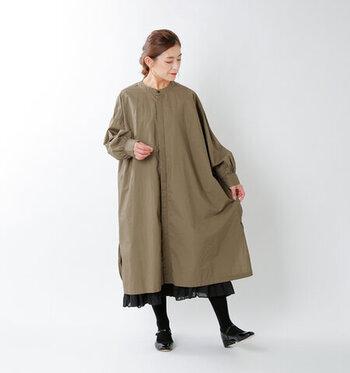 オリーブカラーのワイドシルエットワンピースに、黒のスカートをさりげなくチラ見せしたレイヤードコーデ。タイツやシューズもスカートと同じ黒で揃えることで、脚を長く見せる効果も期待できます。