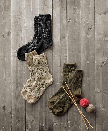 秋らしいカラーとボタニカル柄が可愛い靴下。ローゲージ向きの糸をミドルゲージに編みこむことで、しっかりと目の詰まったウール混のあたたかな靴下となりました。しっかり保温がされておしゃれも楽しめる、これからの季節にはありがたい靴下ですね。