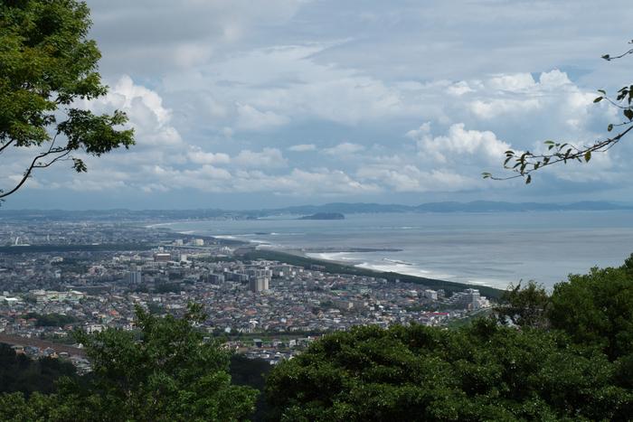 """当コースの魅力の第一は、「湘南平」以降、浅間山、八俵山、高麗山と、3つの頂きを縦走するコースとなっているので、短距離でも、しっかりと""""山登り""""の気分が味わえること。  そして第二は、先の2つのコース同様、視界が開けた場所では、富士山や丹沢山系といった""""山並みの景色""""はもちろん、江ノ島や三浦半島、伊豆大島が浮かぶ""""相模湾の絶景""""も間近に眺められることです。  【9月初旬の「湘南平」からの相模湾と大磯、平塚市街の眺望。「江ノ島」の奥は、三浦半島(逗子・葉山方面)。】"""