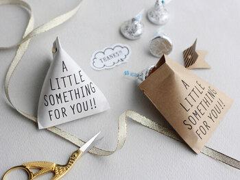 テトラバッグ用のクラフト紙+割りピン+帯が一式セットになっています。お菓子やキャンディなどを入れて封をすれば完成!「A LITTLE SOMETHING FOR YOU!!」は、ちょっとした何かをあなたにという意味。手書き風のフォントで書かれたデザインがおしゃれでたくさん配りたくなりそう。
