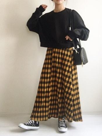 アメカジファッションでシャツに用いられることが多いバッファローチェックをスカートに取り入れ、女性らしいカジュアルスタイルに。アイテムは黒で統一感を出しているので、ベースの黄色がおしゃれに映えていますね。