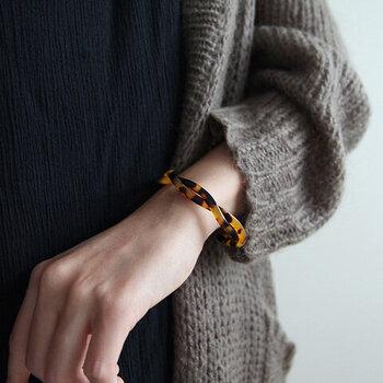 紐を編んだようなデザインが印象的な、透明感が魅力のアセテート素材のバングル。さっとつけ外しができるので、手首が寂しいなと感じたときに活躍してくれます。