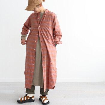 チェック柄のシャツワンピースを、シンプルなワンピースにレイヤード。さらにパンツを重ね着して、暖かさもトレンド感もたっぷりなコーディネートに仕上げています。キャップや靴下×サンダルの組み合わせで、ワンピースの重ね着をカジュアルに。