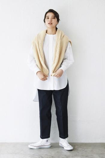 デニムに白シャツを合わせた、カジュアル×きちんと感のミックススタイルです。足元も白のスニーカーでカジュアル色が強めですが、デニムに入ったセンタ―プレスが白シャツとの相性抜群。肩からベージュのニットを羽織ることで、季節感とこなれ感をアップさせています。