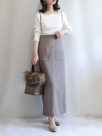 サロペットタイプのタイトスカートが主役のコーデ。子どもっぽくなりそうなサロペットも、細めの肩紐とトップスのスクエアネックで大人っぽい印象に。シンプルなデザインの組み合わせに。ファーのついたバッグがアクセントになっています。