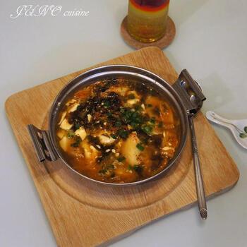 かつおだしにコチュジャン、キムチをアレンジした簡単チゲ鍋です。具材は絹ごし豆腐と海苔、ネギ、卵とどれも火通りが早いものばかり。材料さえ揃えれば、あっという間に作ることができます。  スプーンで食べたくなるひとり鍋ですね。