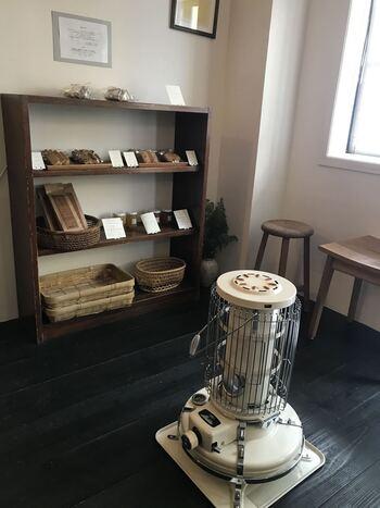 カウンターとテーブル席のこじんまりとした店内。竹かごやストーブなど、レトロなアイテムがセンス良く置かれています。