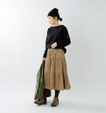 ブラックのスウェットは、シルエットが綺麗なスカートを合わせて全身のフォルムをより美しく。ニット帽でトップにアクセントを作ると、顔周りがよりスッキリした印象に。