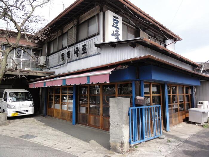 """秦野は農業が盛んな地。中でも""""落花生""""は、日本で初めて落花生が栽培された土地でもあり、秦野の特産物です。肥沃で水捌けが良いので、良質な豆が穫れます。しっかりした味わいは、県外にも名が通っています。  秦野市内には、落花生を販売するお店が多々ありますが、水無川沿いに店を構える「豆峰商店」は、人気有名店の一つ。秦野駅から歩いて5分ほどに店舗があり、「弘法の清水」から「弘法山公園入口」へ向かう途中に店がありますので、時間が合うのなら行きに購入するのも手です。"""