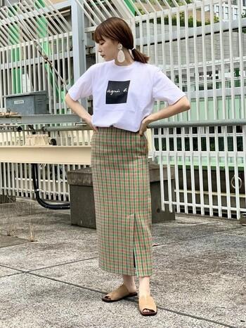 ロゴTシャツがパッと目を引くコーデ。夏らしい明るいチェック柄とロゴTシャツは相性ばっちり。大きめサイズのピアスはまとめ髪にしてしっかりと主張させるのが◎。
