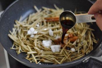 いったん火を止めてから調味料を投入。醤油・砂糖・酒のみのシンプルな味付けです。よく混ぜながら水気が飛ぶまで煮詰め、盛りつけたあとにごまをふりかけて、完成。