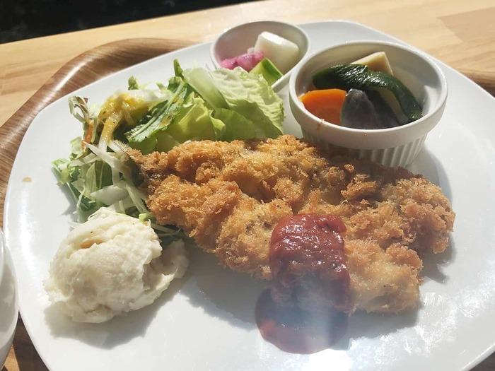"""レストハウスにある「Flat(ふらっと)」は、""""ハイキングやドライブで訪れた方がふらっと寄りたくなる、くつろぎカフェレストラン""""。江ノ島や大島が浮かぶ相模湾を望む店内は、明るくカジュアルな雰囲気です。 【色とりどりの新鮮野菜が添えられた『かますフライ』。鮮魚も地元産で、新鮮美味。】"""