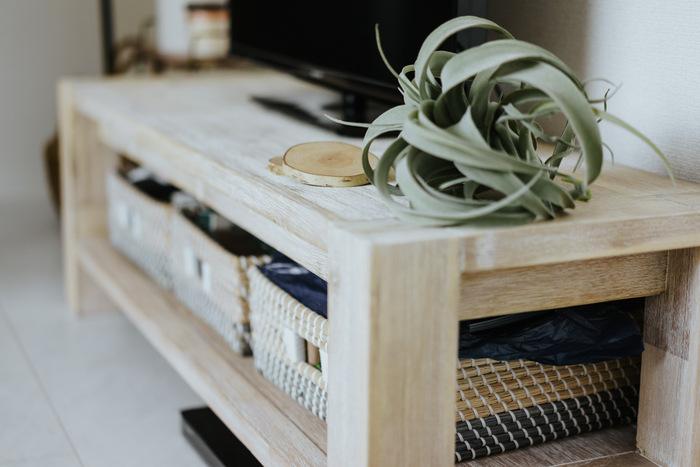 ナチュラルな白木のテレビ台は「unico」のもの。収納はバスケットを使用してざっくりと。台の上にはテレビと一緒にフェイクグリーンを飾ってナチュラルな印象に。
