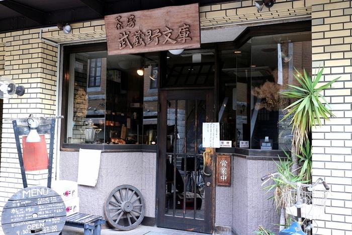 """吉祥寺駅から、5分ほど歩いた場所にある「茶房 武蔵野文庫」は、""""秘伝のカレーが絶品""""との定評があるお店です。創業は1985年。かつて、早稲田大学の近くにあった喫茶店「茶房 早稲田文庫」から引き継がれ、今の店名になったそう。大学の表札を彷彿とさせるような、立派な木の看板が目印です。"""