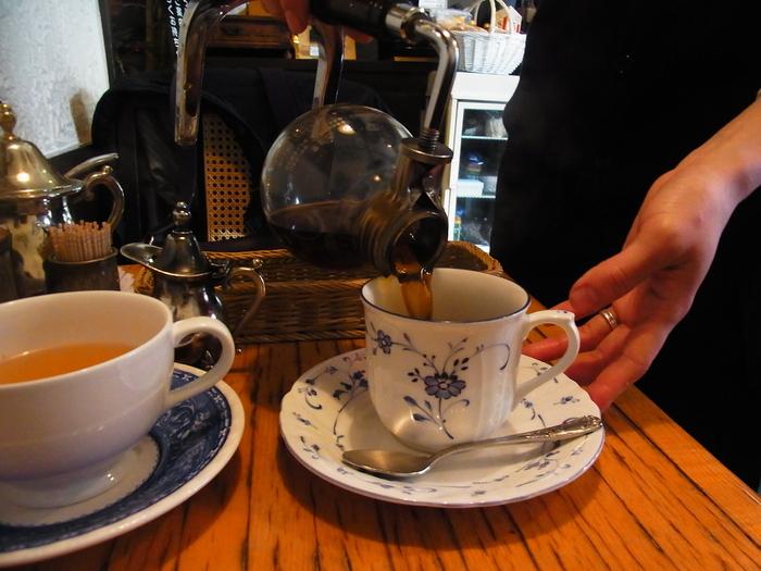 テーブルにてサイフォンで注がれるコーヒー。ブレンドコーヒーは、深いコクと強い苦みの中にも酸味と甘みをほどよく感じられる、バランスのとれた一杯です。